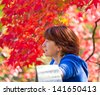 Thoughtful women on blurry autumn background - stock photo