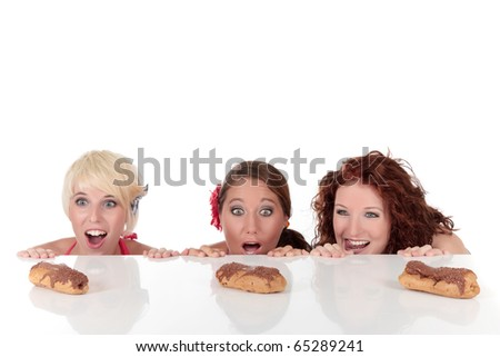 Three attractive young woman being tempted, longing for an eclair, peeping above table. Studio shot. White background. Shallow dof