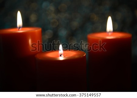 three big aromatic candle light up in front of beautiful bokeh background, valentine's day