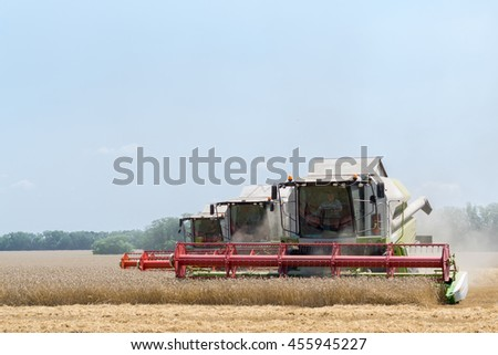 Three big modern harvesters harvest yellow wheat field on sunny summer day