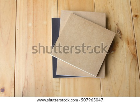 three books,on brown wooden,top view