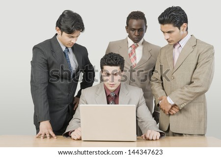 Three businessmen looking at their colleague using a laptop