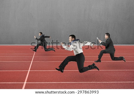 Three businessmen running on red track, with gray concrete wall background.