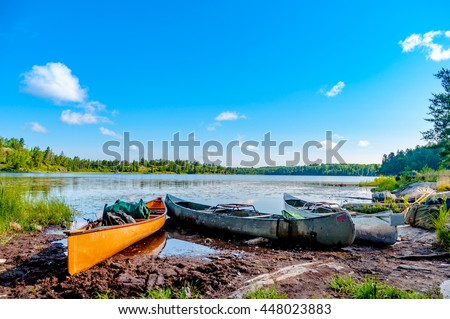 Three canoes on the shore of a lake in the Boundary Waters Canoe Area in the North Woods of Northern Minnesota wait for the paddlers to return from a portage.
