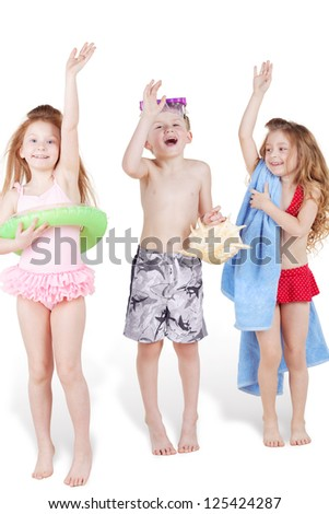 Three children in beach suits with beach accessories, boy and two girls, waves their arms and shouts, standing on tiptoes, focus on boy