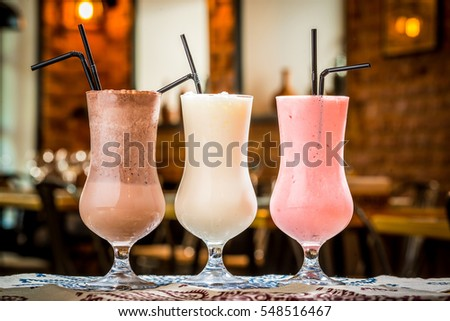 three cocktails in plastic cups with straws in the bar