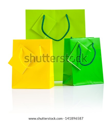 three colored paper bags isolated on white