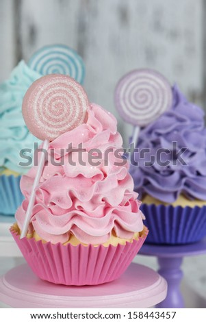 Three colorful cupcakes with lollipops