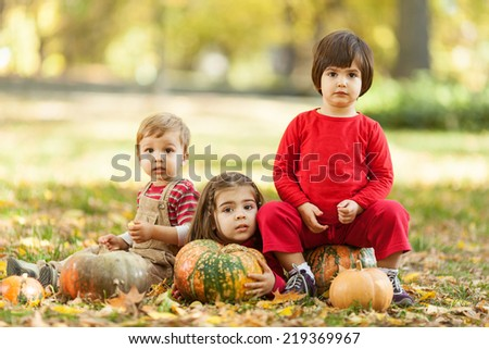 Three cute little children portrait in a autumn park.