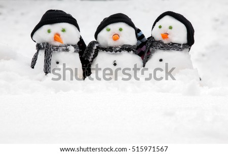 Three cute snowmen in a row sat in the snow wearing hats and scarfs huddled together. Copy space for text below each snowman. Carrots for noses and peas for eyes.
