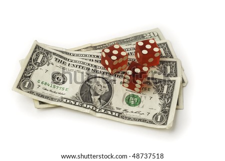 Three dice and some dollar bills shown from a slight overhead angle on white background. Saved with clipping path