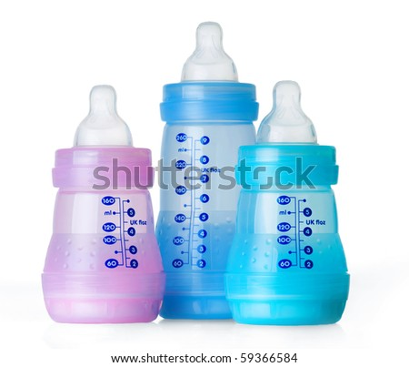 Three empty baby bottles isolated on white background with measurement markings in ml and oz