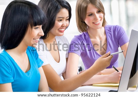 Three female friends studying together in a classroom