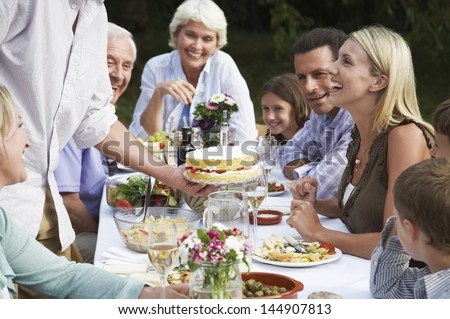 Three generation family celebrating birthday of woman at dining table outdoors