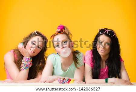 Three girls are having fun together, yellow background