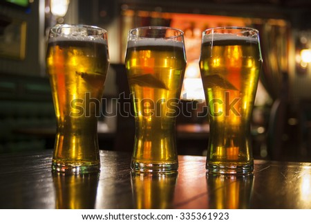 Three Glasses of Beer on a Table in  Pub