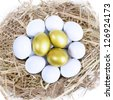 Three golden eggs inside a nest, surrounded by white eggs - stock photo