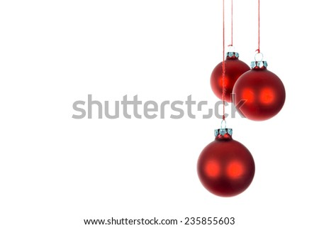 Three hanging Christmas balls over a white background