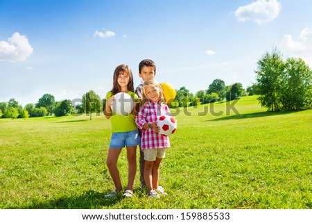 Three happy kids, boy and girls standing in the sunny summer park holding sport balls
