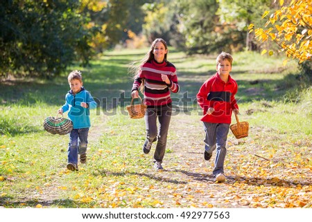 Three happy kids running on autumn forest with baskets for mushrooms