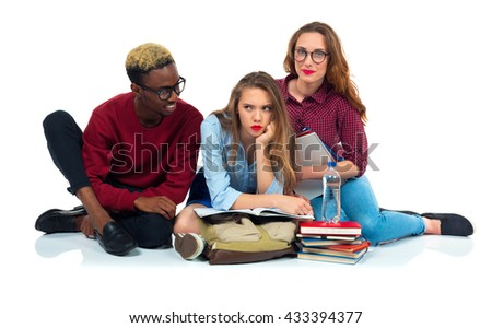 Three happy young teenager students with books, laptop and bags isolated on white background