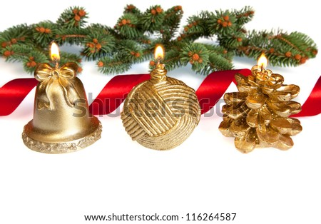 Three isolated burning golden candles with the shapes of pinecone, Christmas ball and bell, decorated with green pine and red ribbon.