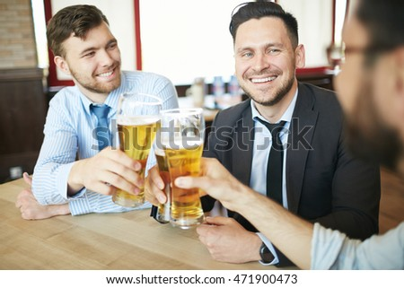 Three laughing businessmen in formal clothes having beer in bar after work celebrating with clinking glasses