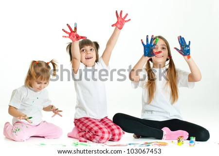 Three little happy beautiful girls (sisters) painting on white background