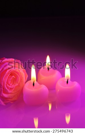 three luminous pink candlehearts with pink rose in purple light