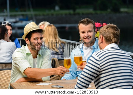 Three male friends relax drinking beer night out restaurant terrace