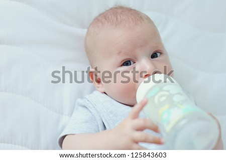 Three month old baby boy drinking milk from his bottle