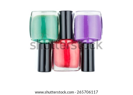 Three multi-colored nail polish, red, turquoise and purple lie on a white background