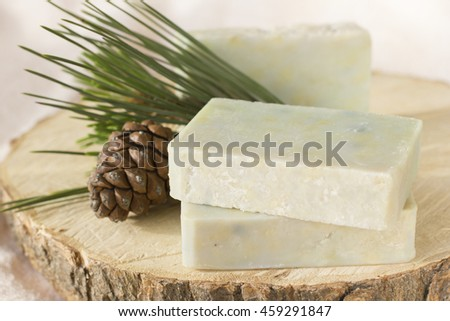 three natural soaps with a branch and the cone of a pine on a light background. Soaps contain essential oil of a pine for care and treatment of skin