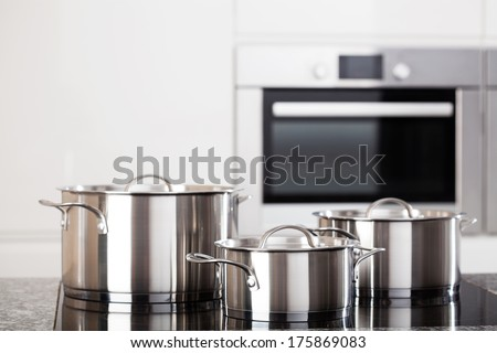 Three new metal pots in the kitchen on induction hob on modern kitchen background