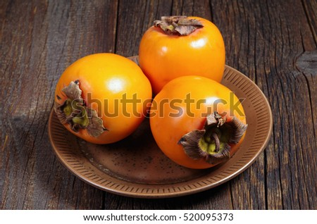 Three orange persimmon fruits in plate on old wooden table