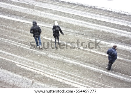 Three people crossing the empty boulevard during the snowstorm, high angle view