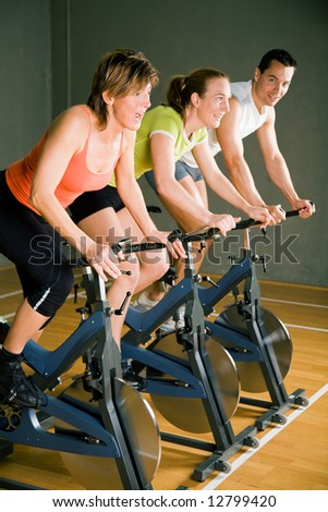 Three people cycling in a gym or fitness club, dressed in colorful clothes; focus on the mature woman in front
