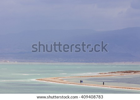 Three people walking on headland between the turquoise waters on dark stormy day at Dead Sea with mountains on background