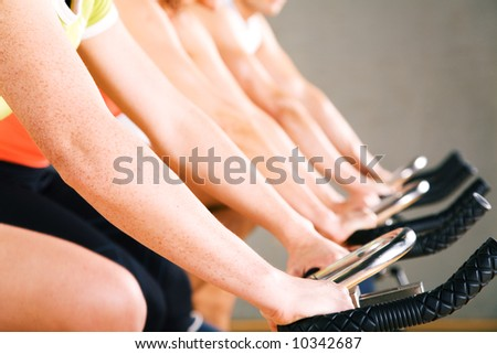 Three people working out on a stationary bicycle in the gym