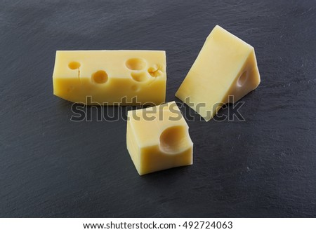 Three pieces of cheese on a black stone slate plate