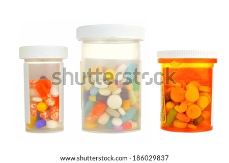 Three pill bottles filled with assorted medications isolated on white
