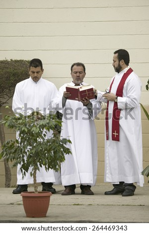 Three priests reading from the bible on Good Friday, Easter,Our Lady of Guadalupe Parish, Oxnard, California, April 6, 2007.
