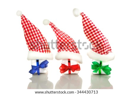 Three red and white, blue and white and green and white checkered santa hats and three white gifts with colored ribbons isolated in front of white background