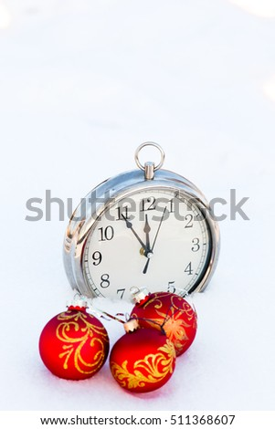 Three red christmas balls and clock on a snow. New Year greeting card concept. Copy-space