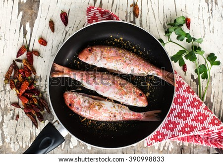 three red mullet with hot spices and parsley inside pan ready for cooking