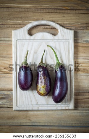 Three ripe eggplant selected to cook on a wooden chopping board top view