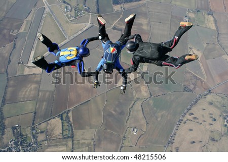 Three skydivers performing formations