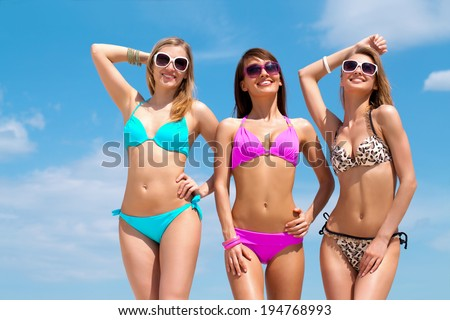 Three slim young girls in bikinis on the beach