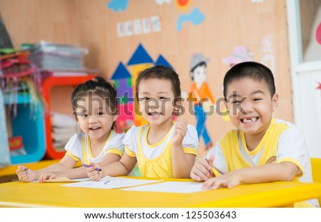 Three smiling children sitting at table in the kindergarten