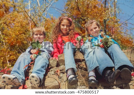 Three smiling kids sitting on a stone wall in an autumn garden